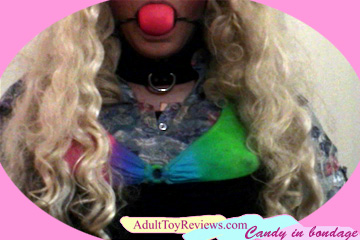 Candy in bondage with ball gag, blonde wig, leather collar, and colorful bra